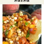 Corn and Peach Salsa in a bowl surrounded by peaches.