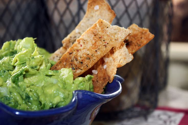 Herbed Pita chips in a bowl of guacomole