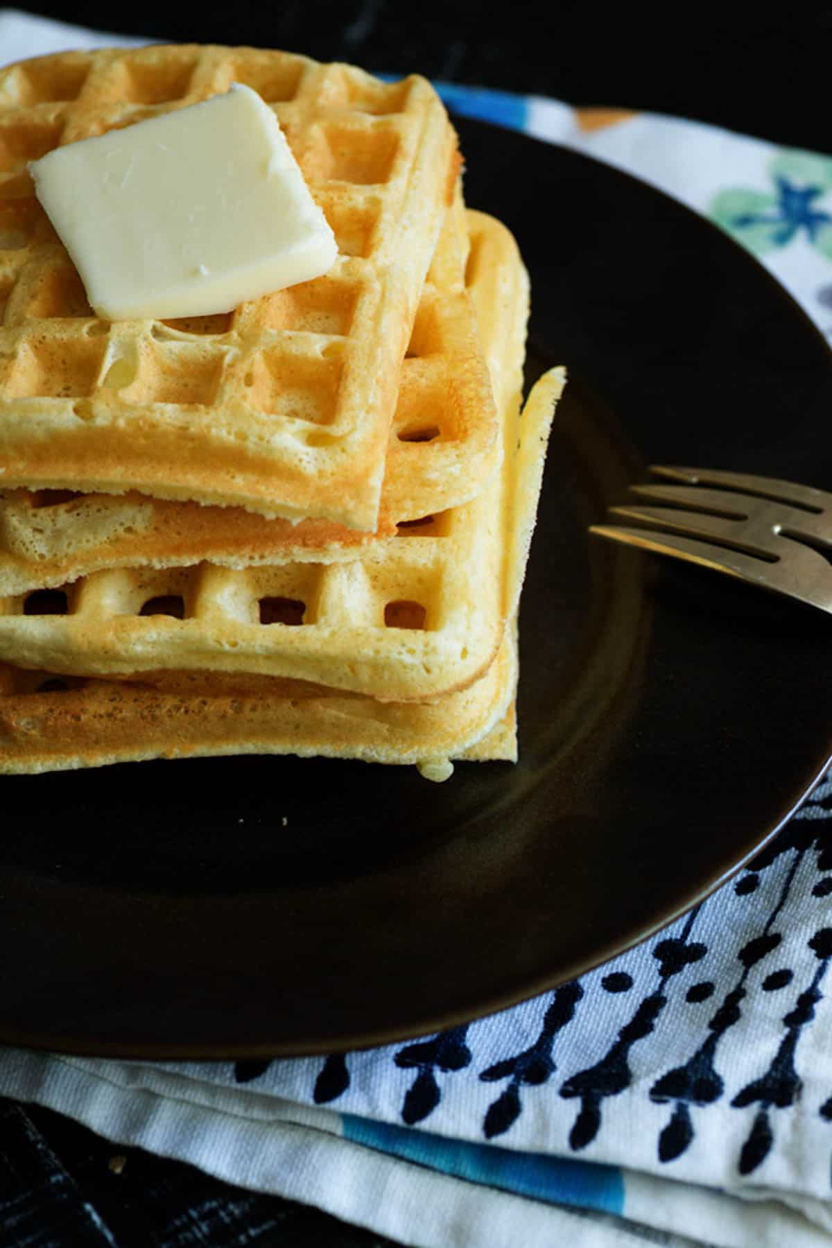 A stack of waffles with butter on top.
