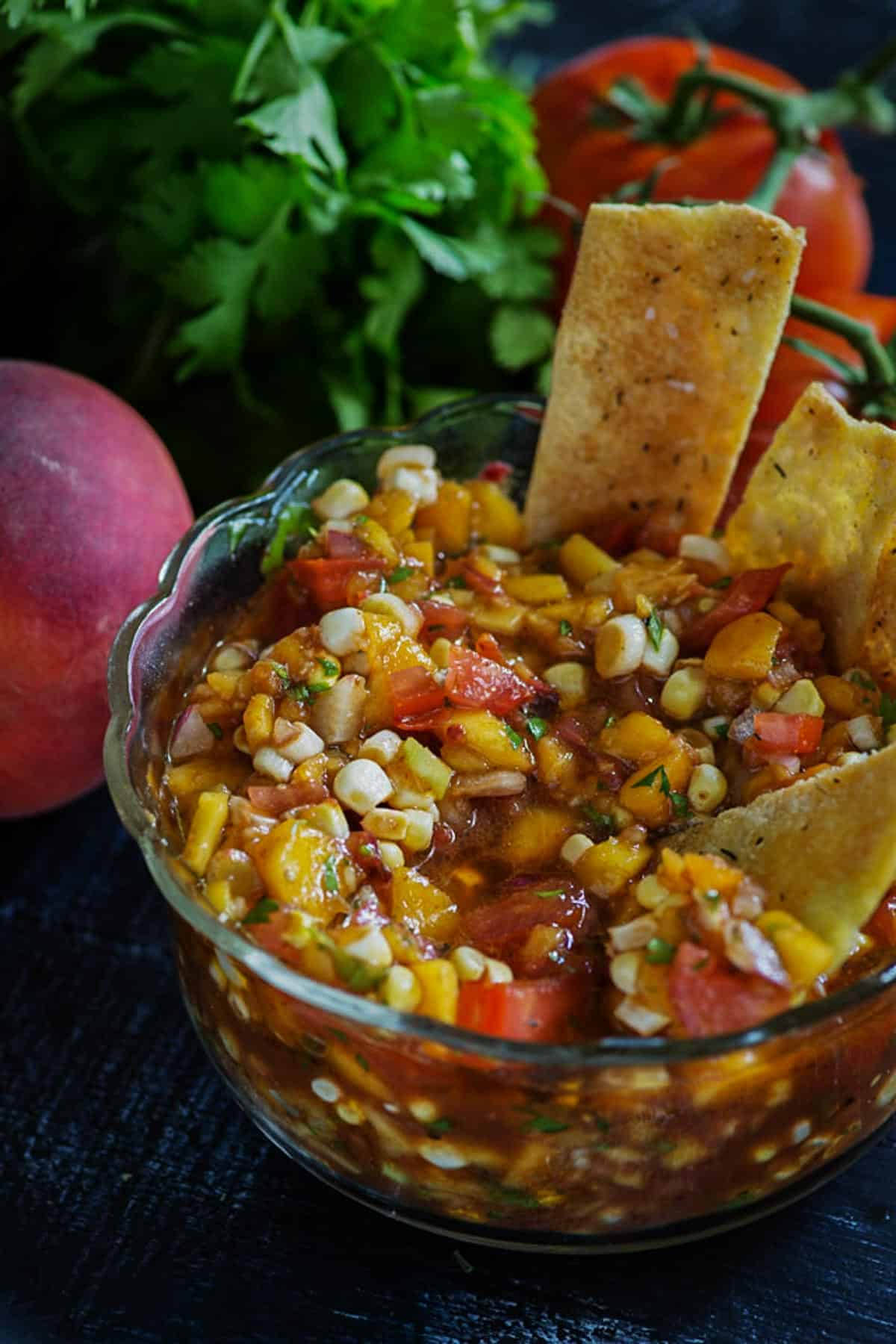 Peach Salsa in a bowl with homemade pita chips