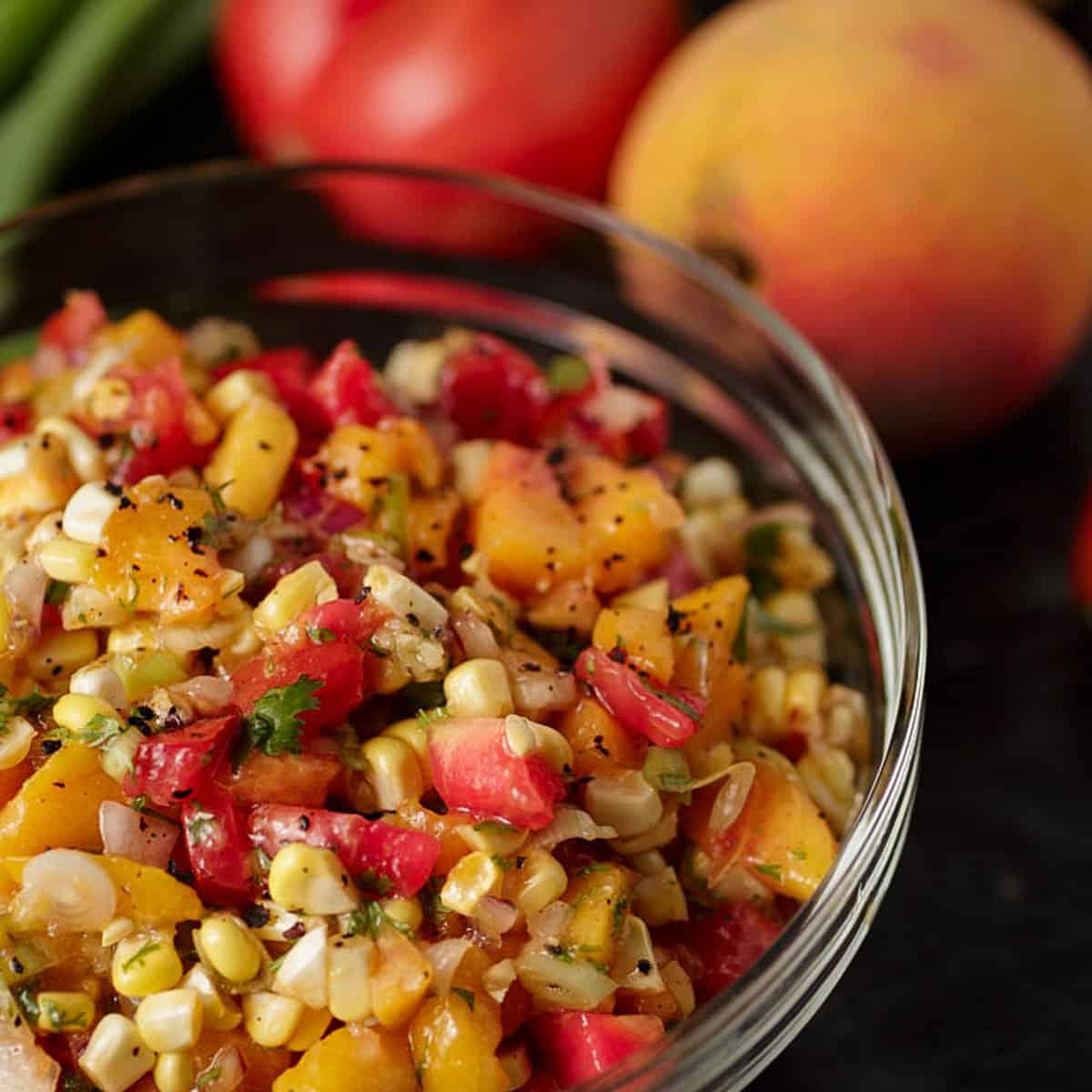 A glass bowl of peach and corn salsa