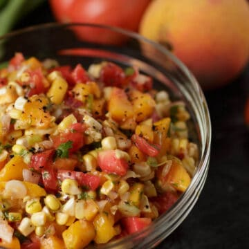 A bowl of corn and peach salsa with peaches and tomatoes