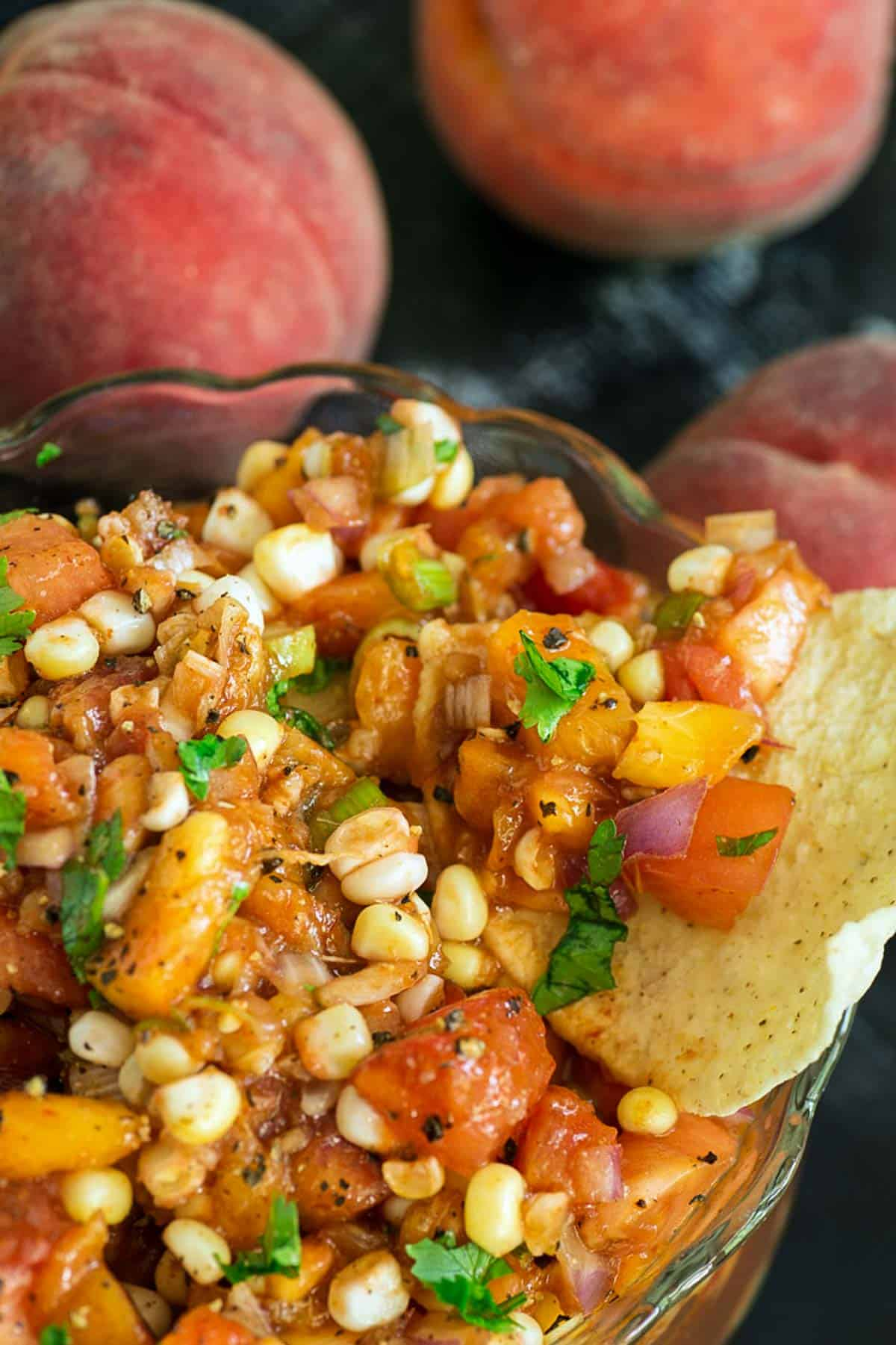 Peach and corn salsa in a bowl with tortilla chips