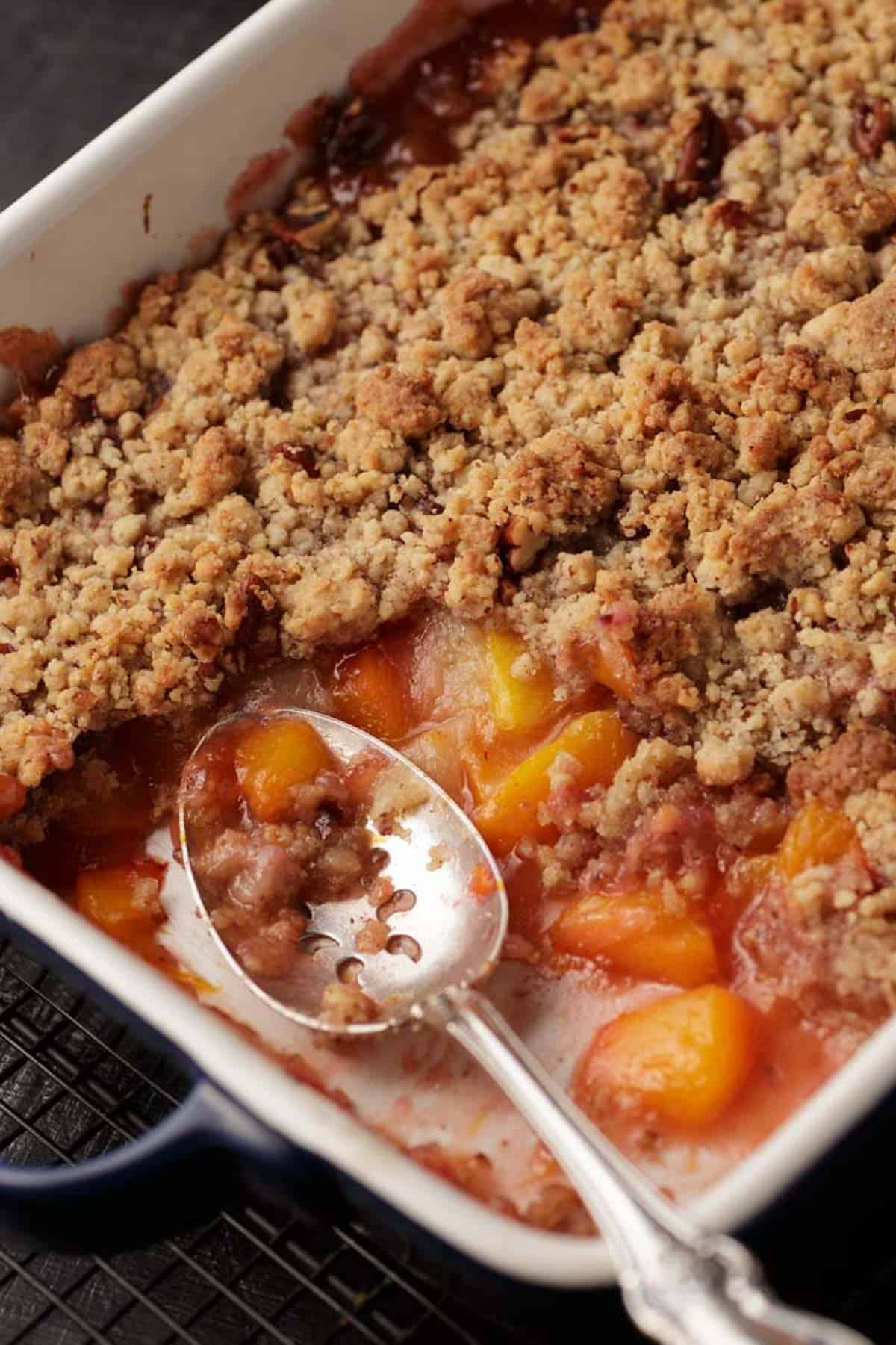 A baking dish of peach crumble with a serving removed.