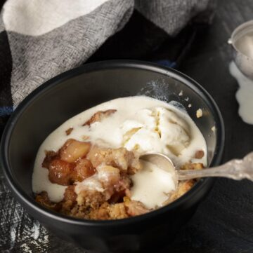 A bowl of peach crumble with pecans with melted ice cream on top.