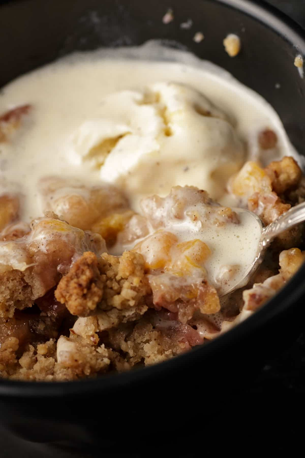 A spoon full of peach and pecan crummble.