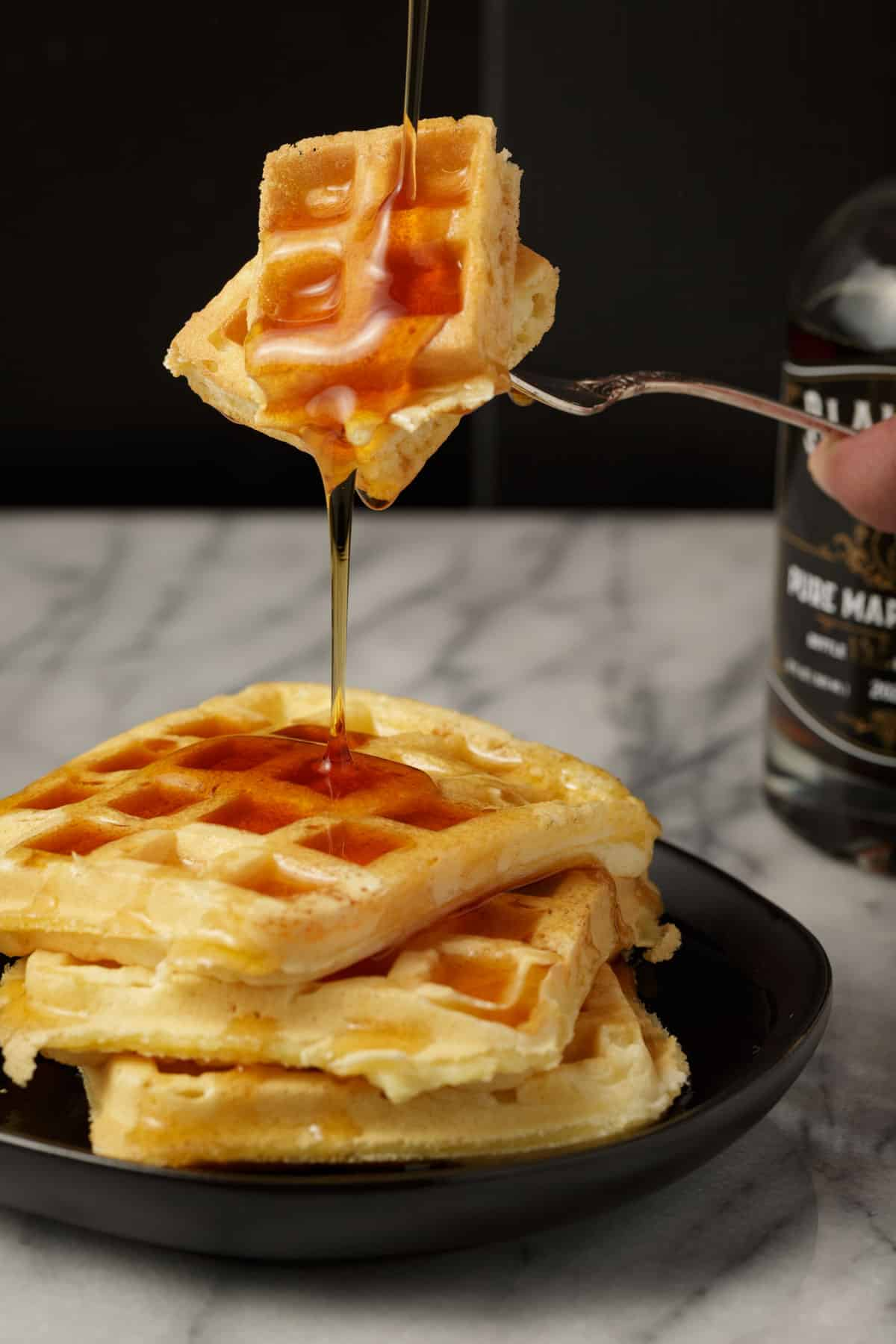 A bite of a homemade waffle with syrup dripping off of it.
