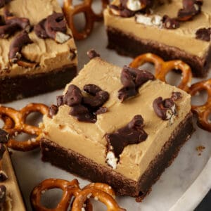 A peanut butter frosted brownie with pretzels on the top and around the sides