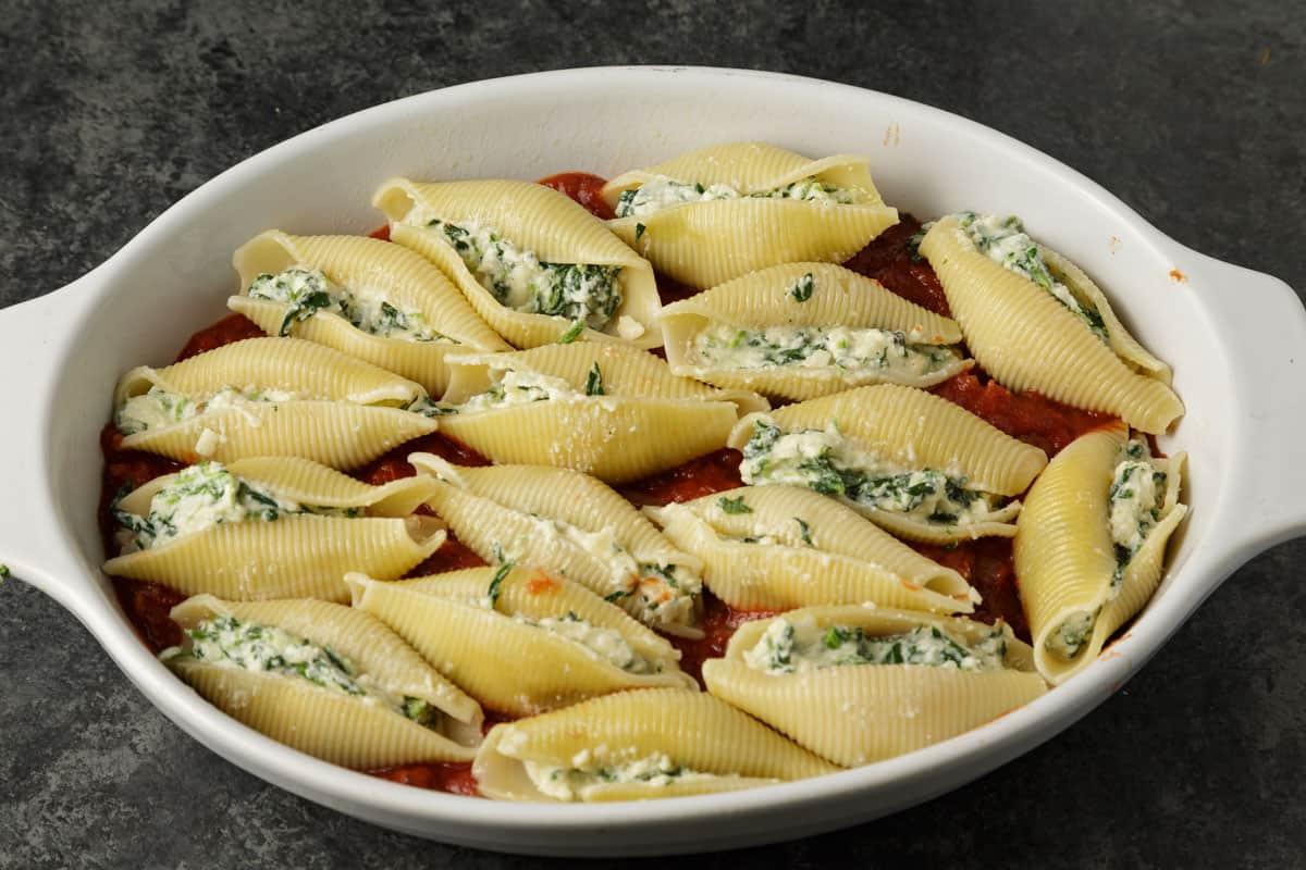 Stuffed shells on a layer of sauce in a baking dish