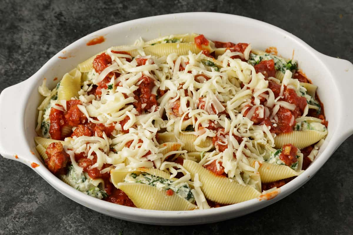 A baking dish of stuffed shells covered with cheese before it is baked