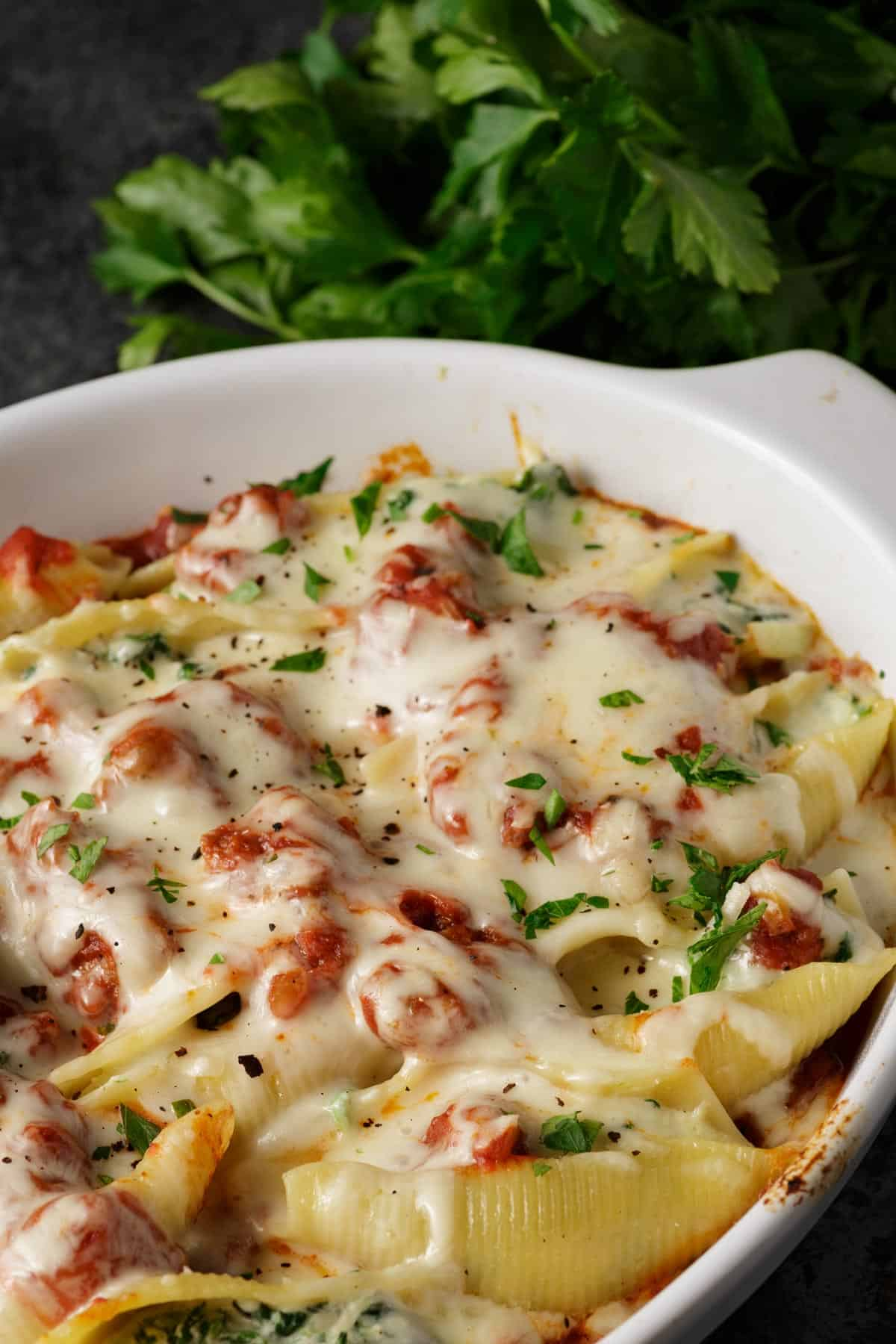 A baking dish of cooked stuffed shells with spinach and ricotta