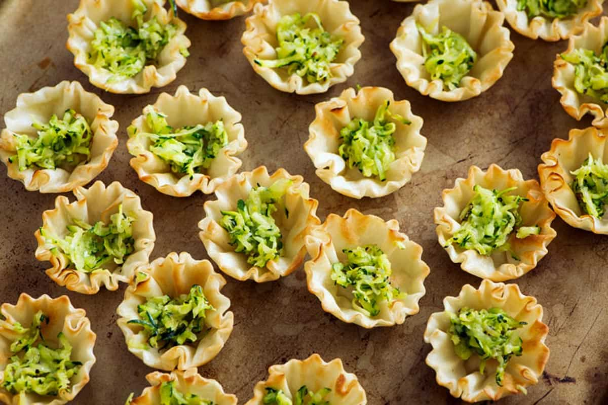Phyllo cups filled with grated zucchini.