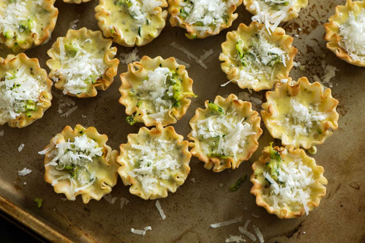 Filled phyllo cups with cheese sprinkled on top.