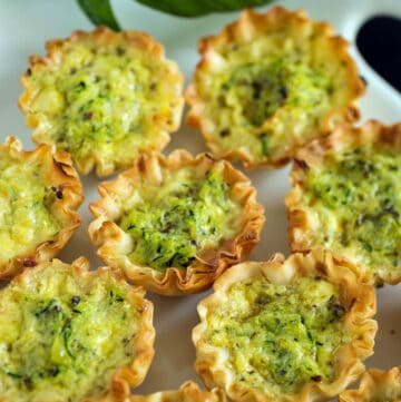 Zucchini quiches on a white serving platter.
