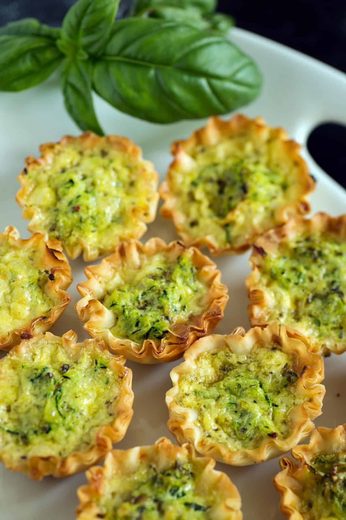 A platter of zucchini quiches with basil leaves.