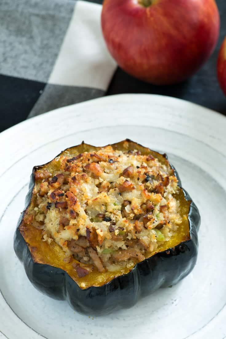 Baked Acorn Squash on white plate beside apple