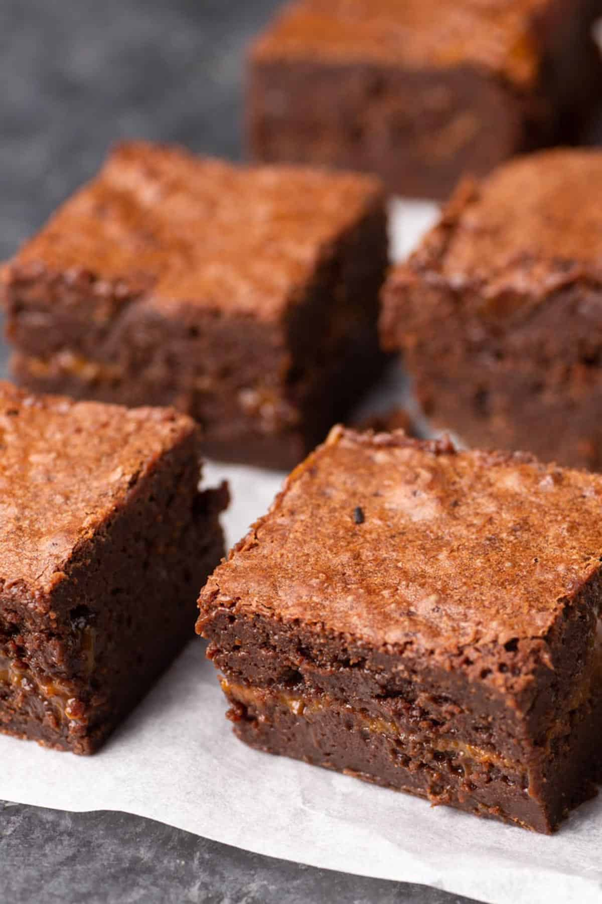brownies with a layer of dulce de leche on parchment paper
