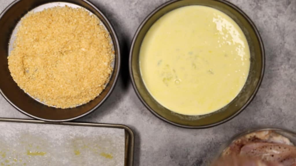 two cake pans with ingredients for dipping chicken