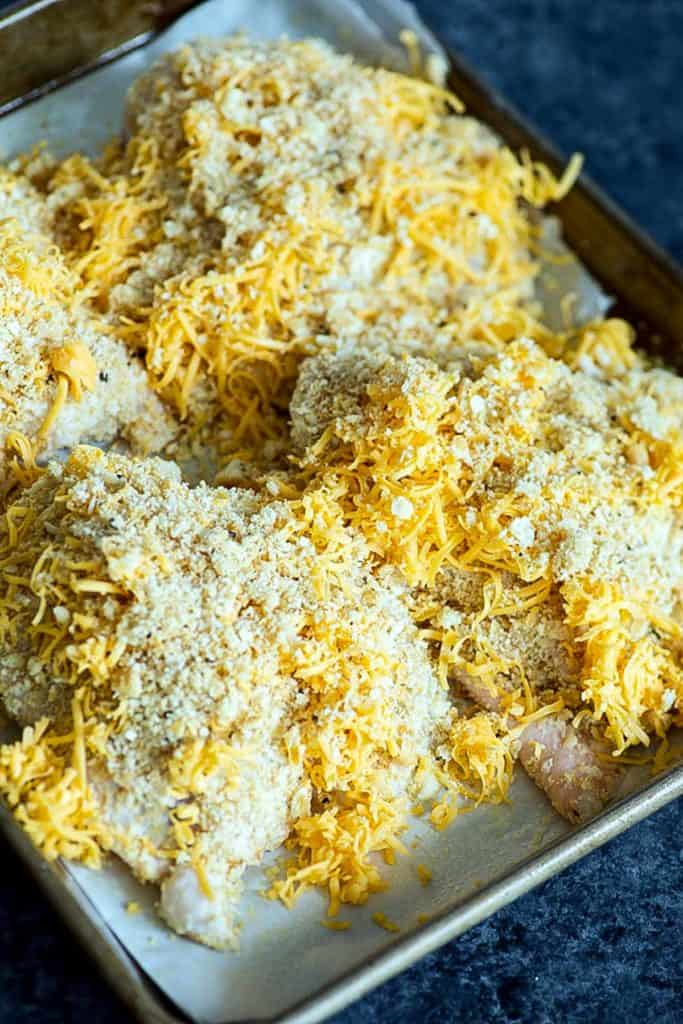 Chicken coated with crackers and cheese on a baking sheet