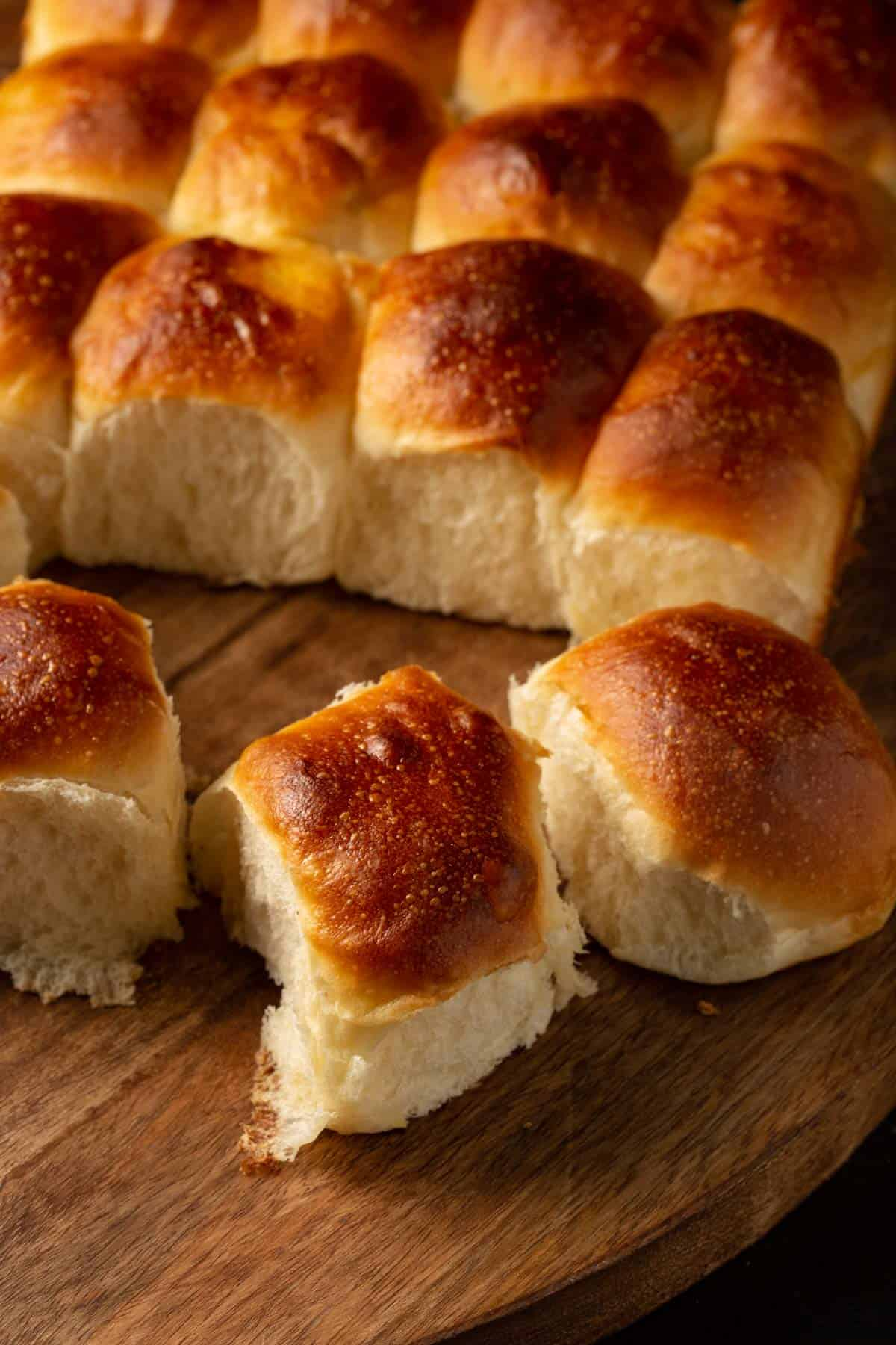 A batch of challah rolls on a wooden board.