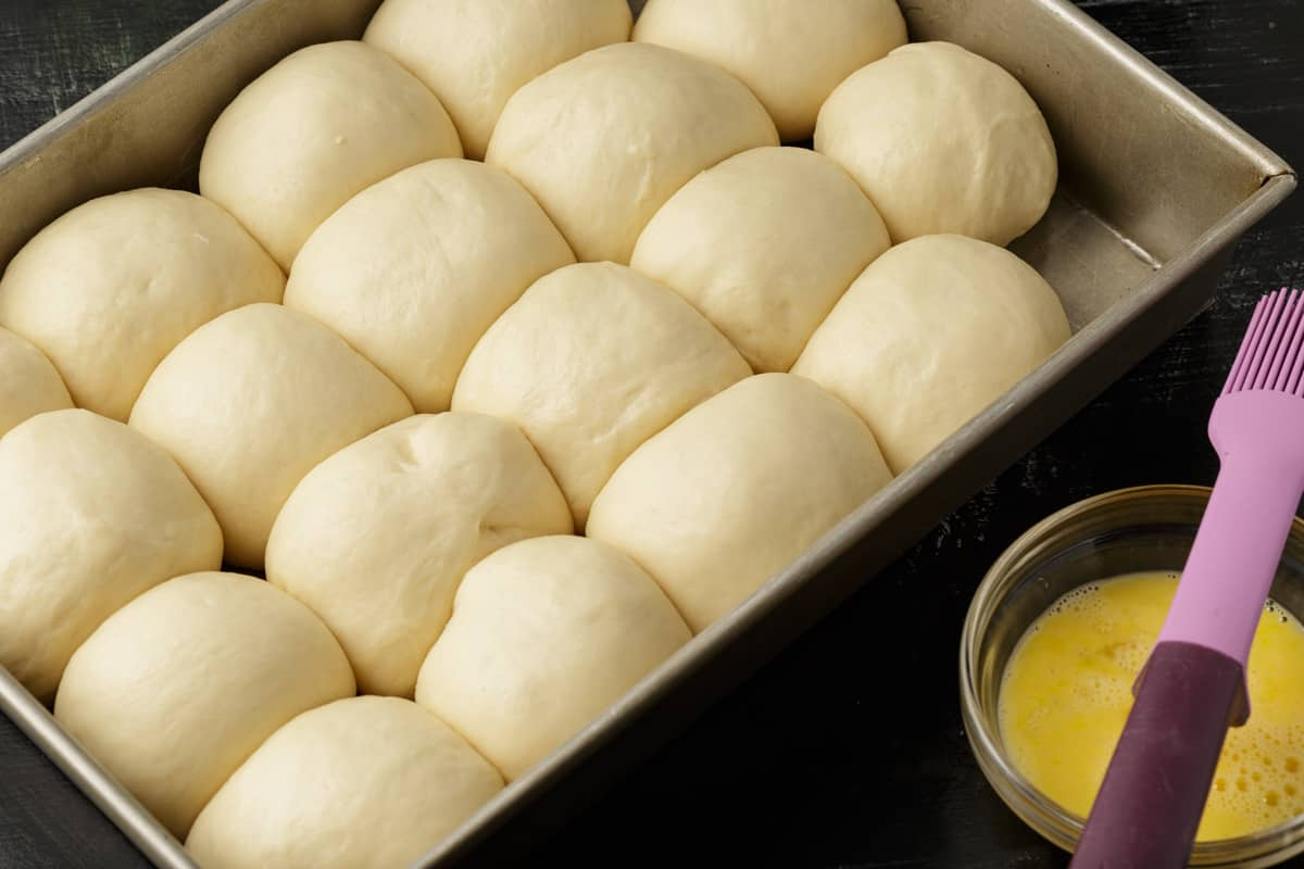 Risen rolls in a baking dish before the egg wash has been added.