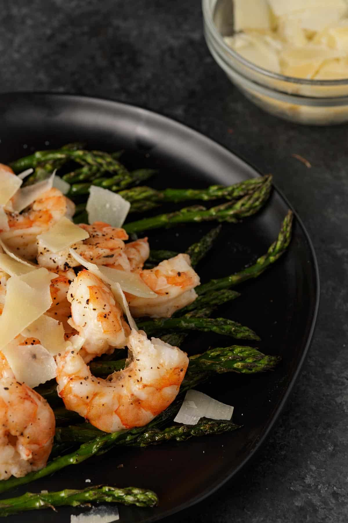 A platter of oven roasted shrimp on asparagus with a bowl of cheese