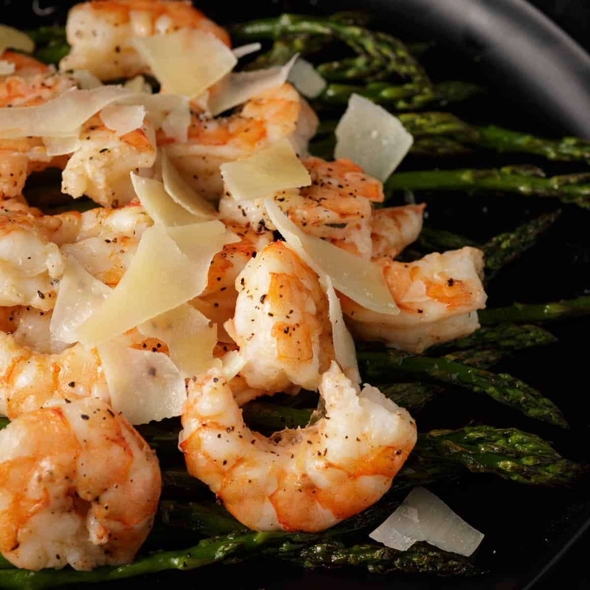A platter of oven roasted shrimp and asparagus