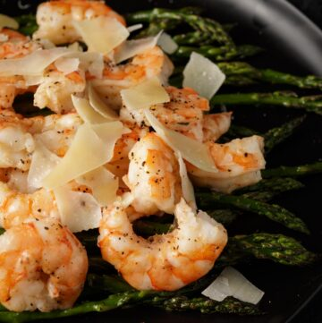 oven roasted shrimp over asparagus on a platter