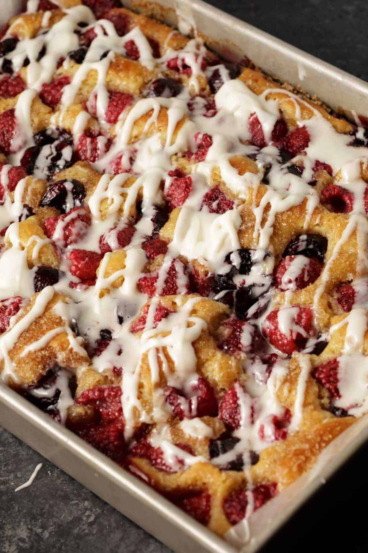A baking pan of fruit filled coffee cake with icing.