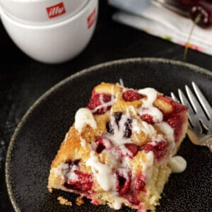 A serving of cherry and raspberry coffee cake with icing drizzled on top.
