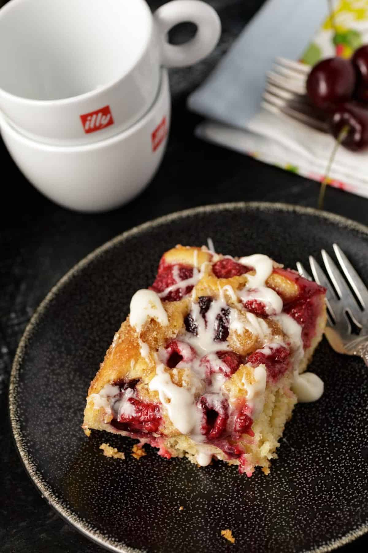 A serving of cherry coffee cake with cups for coffee to the side.