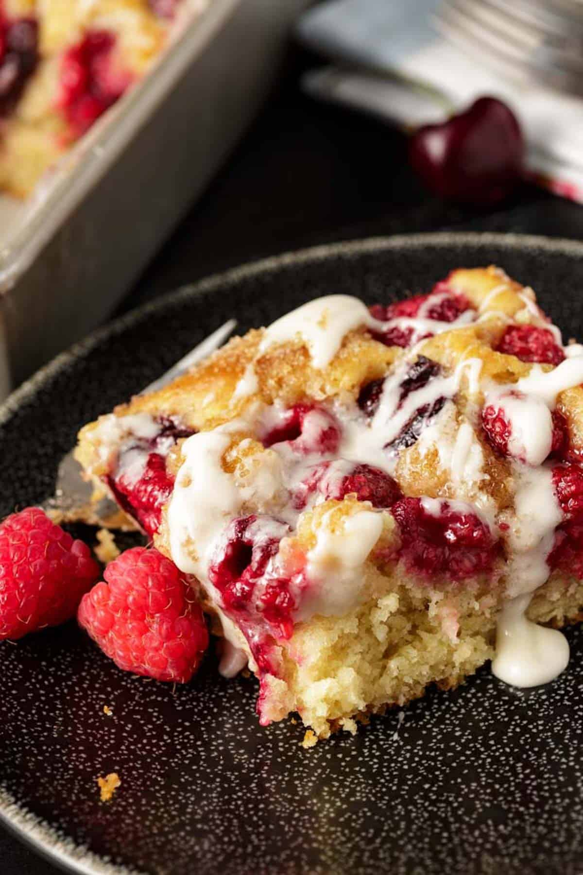A square serving of coffee cake with raspberries on the side.