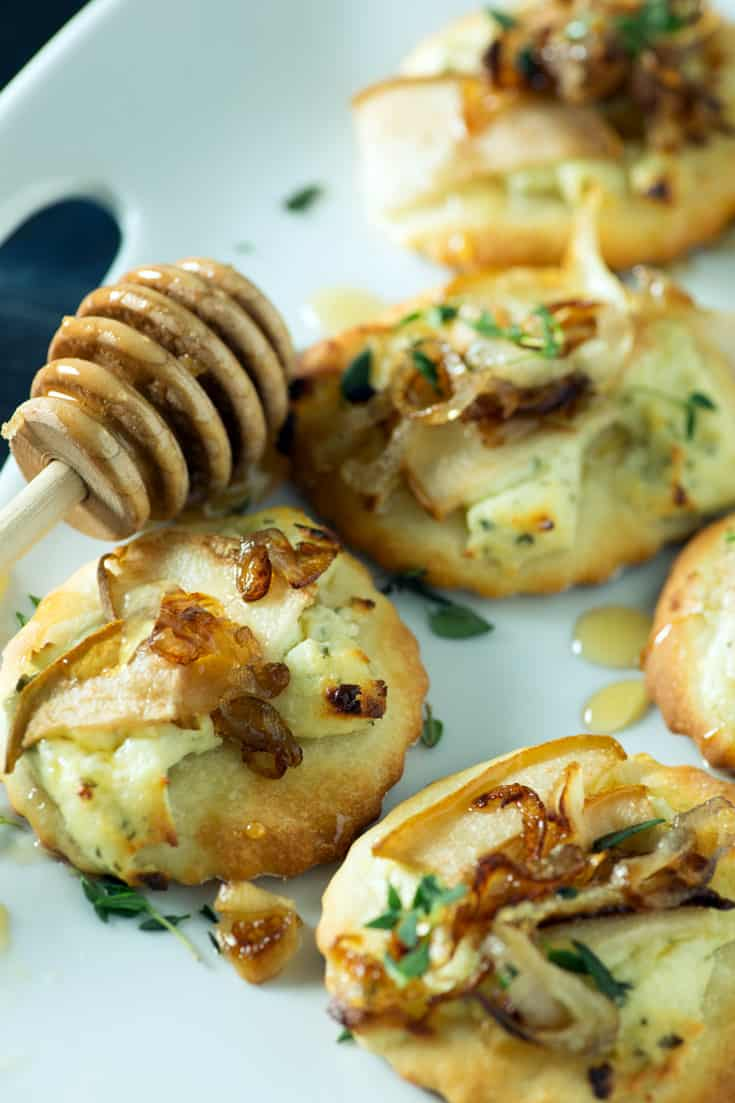 Pear mini pizzas with caramelized shallots on dish with honey spoon