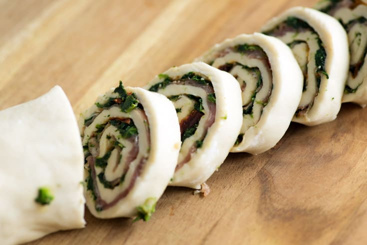 Sliced Pinwheels with spinach, prosciutto and sun dried tomatoes before baking