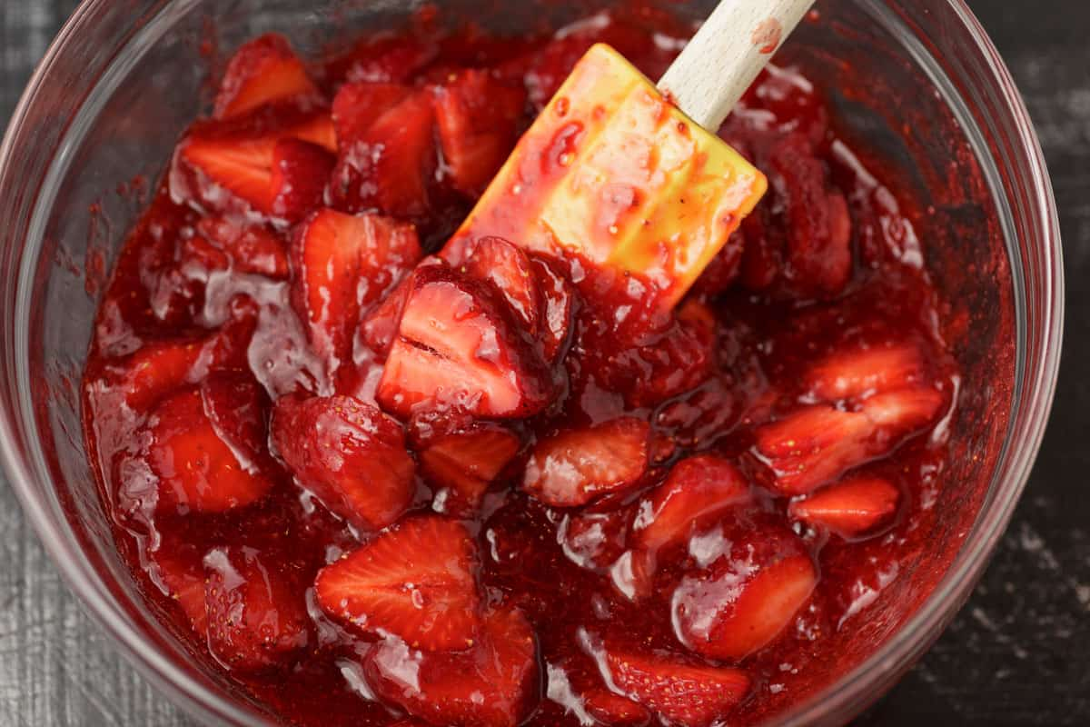 A bowl of cooled pie filling with fresh strawberries