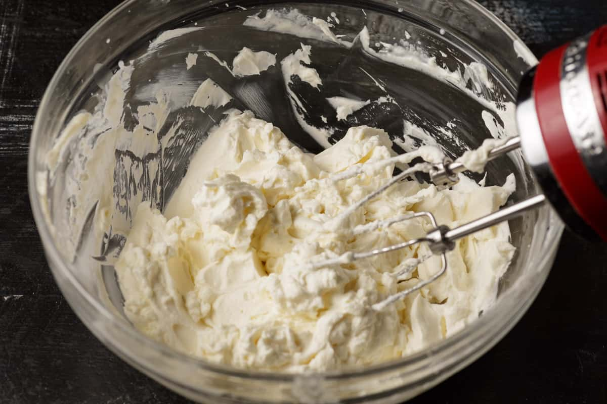 A bowl of whipped cream with cream cheese with beaters.