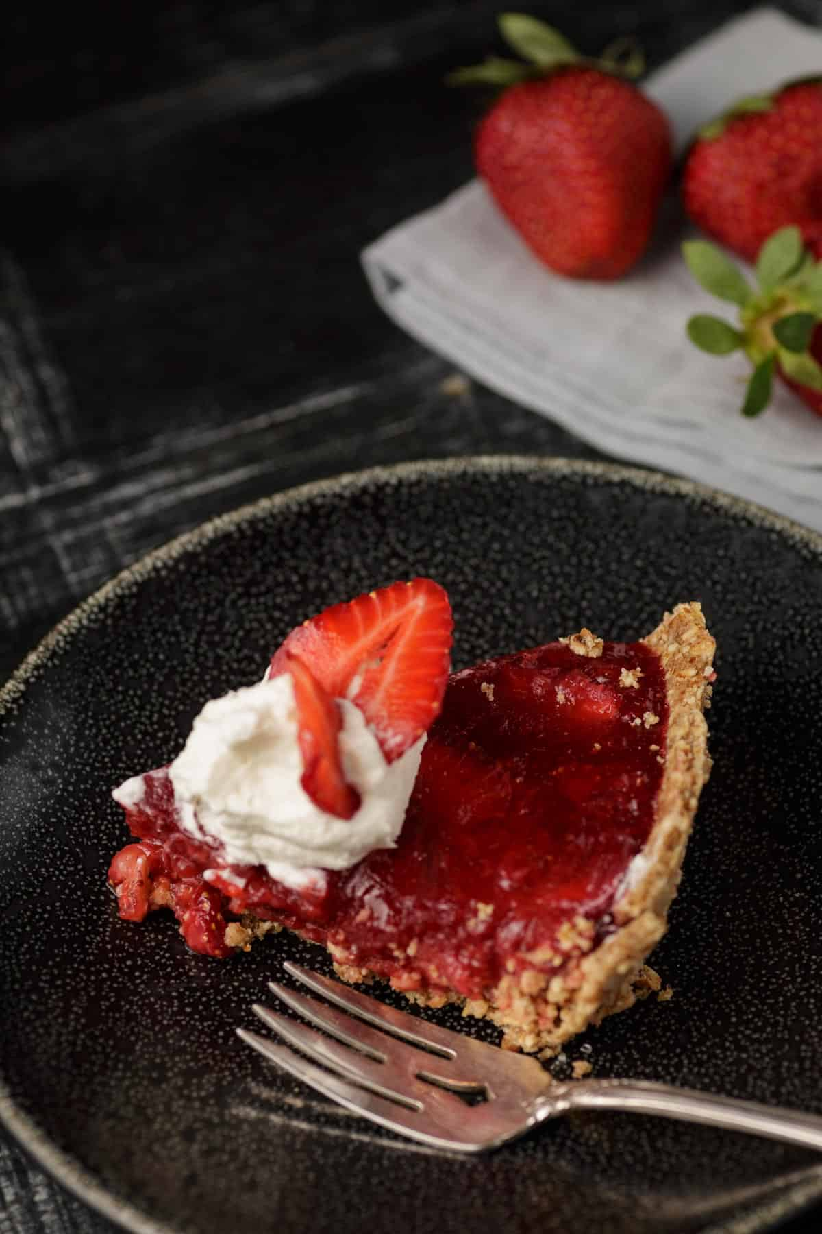 A slice of strawberry pie with whipped topping on a plate with a fork