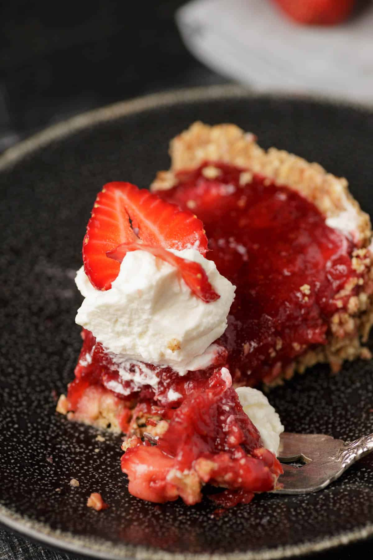 A bite of strawberry pie on a fork