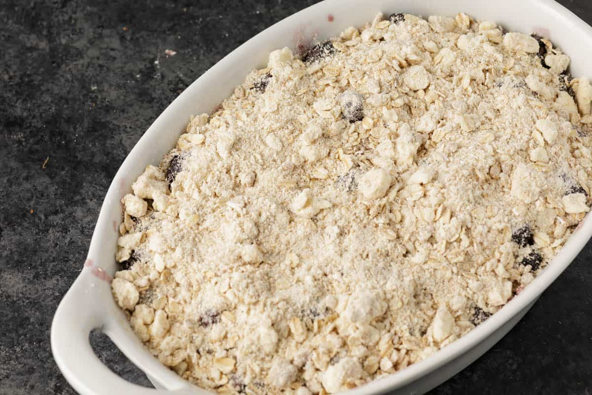 A baking dish with a recipe of blackberry crisp before it is baked