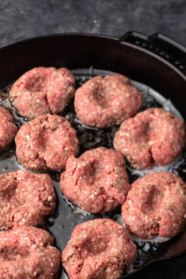 A skillet of hamburgers cooking for Spicy Bourbon BBQ Sliders