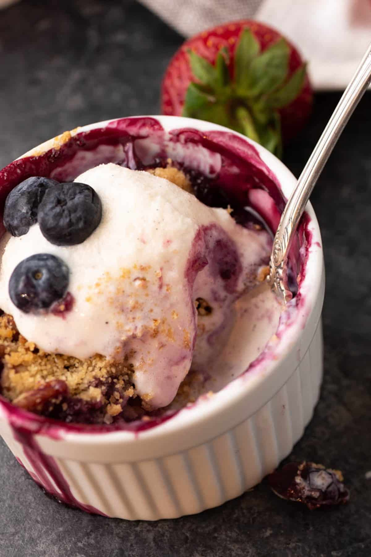 Ice cream topped berry and rhubarb crisp with a spoon