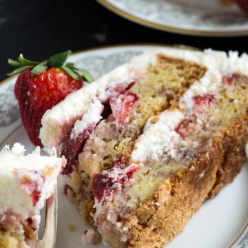 A bite of a piece of strawberry cake with cream cheese frosting