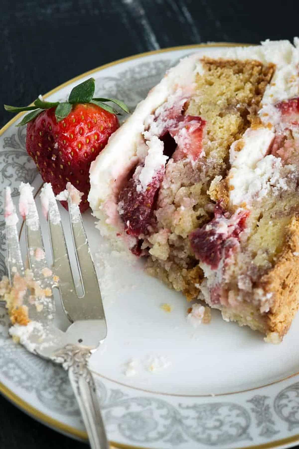 A half eaten slice of strawberry shortcake