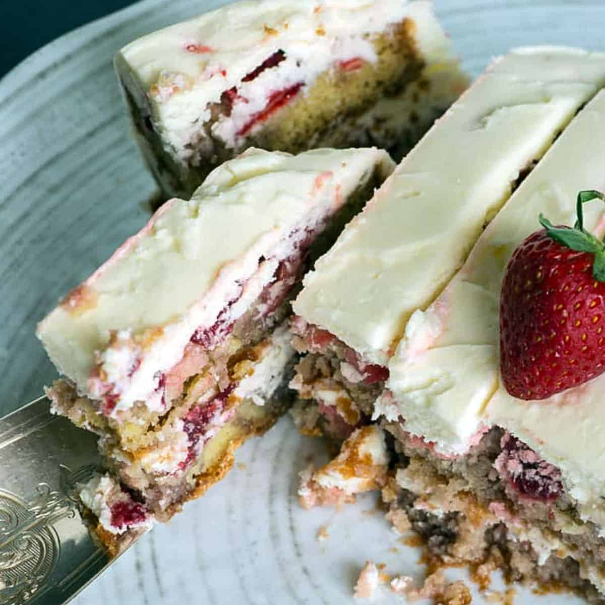 A slice being pulled out of a strawberry cake