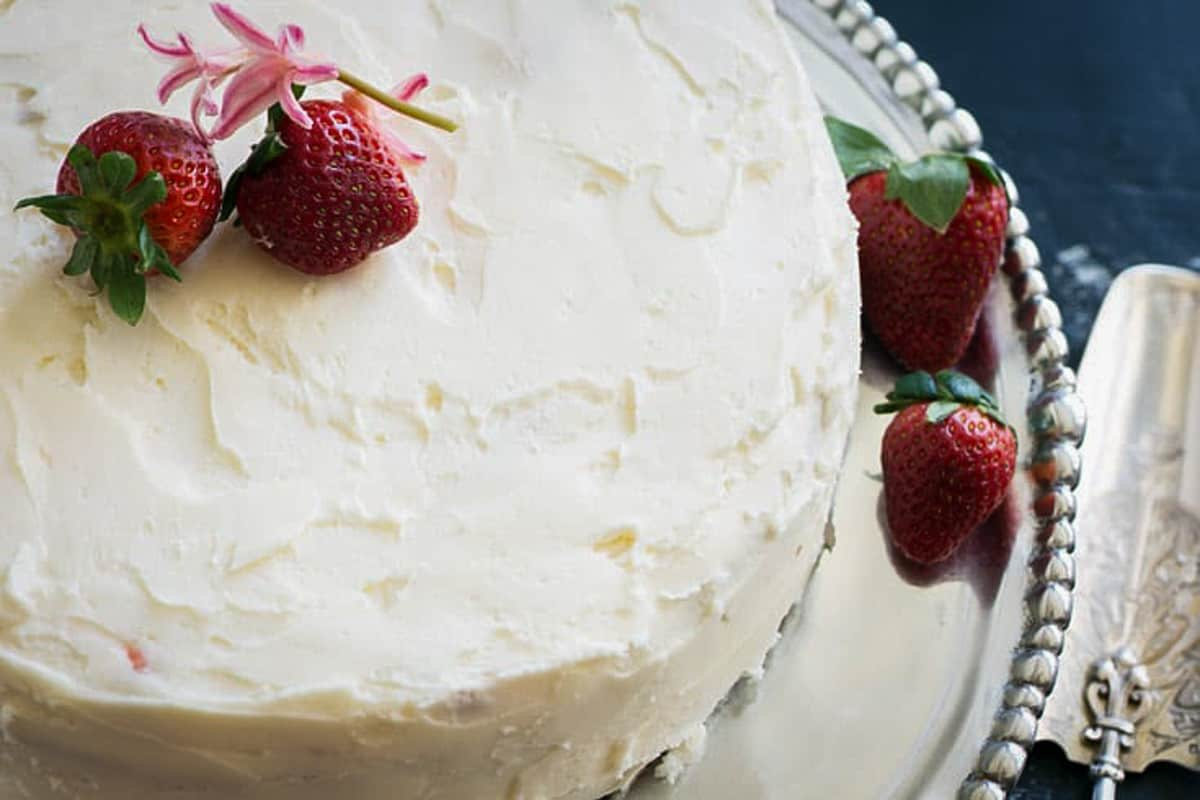 A fully frosted strawberry cake with strawberries on top