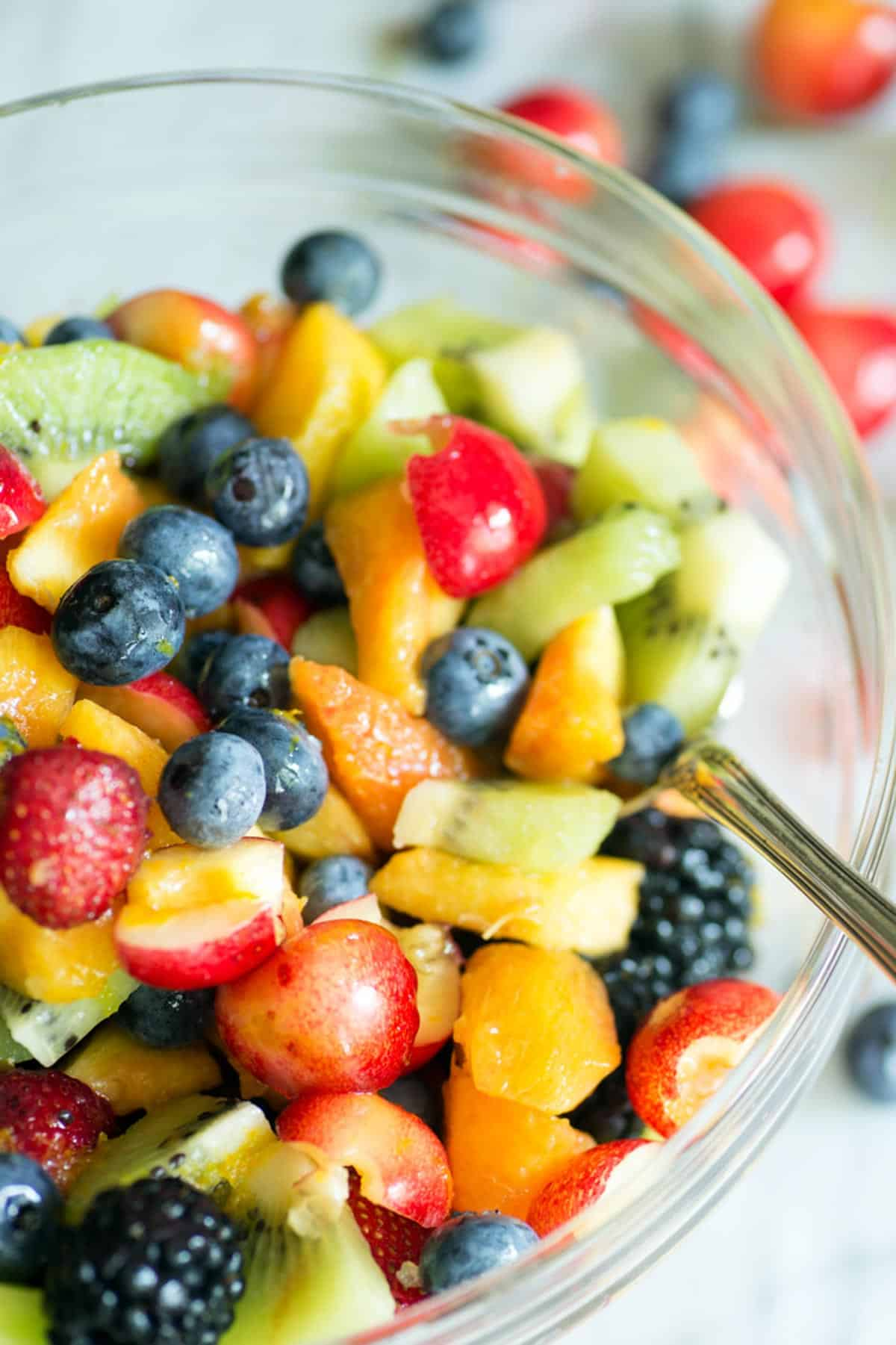 A glass bowl of summer fruit salad with a spoon.