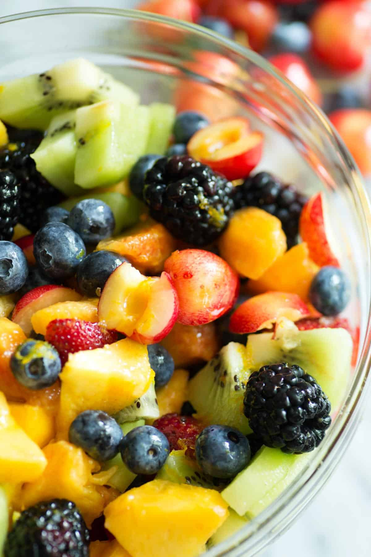 fruit salad with honey lime dressing in a bowl with cherries in the background.