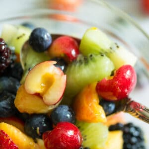 A spoonful of fruit with a honey lime dressing poured over it.