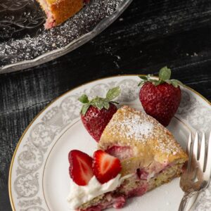 A slice of lemon strawberry Shortcake on a plate with a fork