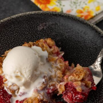 Strawberry crisp with vanilla ice cream on a plate with a flowered napkin
